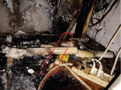 Photo provided by the fire department. The red outline shows the power bar location on the plywood shelf viewed from the front of the shelf.
